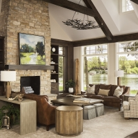stone fireplace,. great room, leather sofas, cocktail table, side table, book cases, rug, console table, table lamp, arm chair, ottomans, pillows, accessories, lake view, chandelier