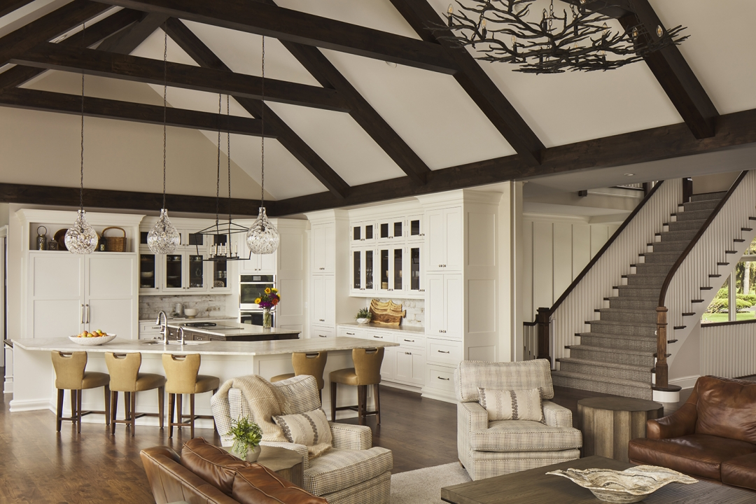 great room kitchen, white kitchen, beaned ceiling, wood floor, island stools, two islands, pendant lights, glass front cabinets, armchairs, stairway, ship lap, chandelier