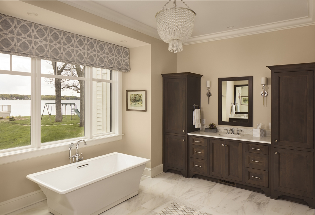 master bath, freestanding tub, rectangular tub, stained wood cabinetry, vanity, beaded cahndelier, window treatment, geometric fabric, sconces, mirror, marble floor