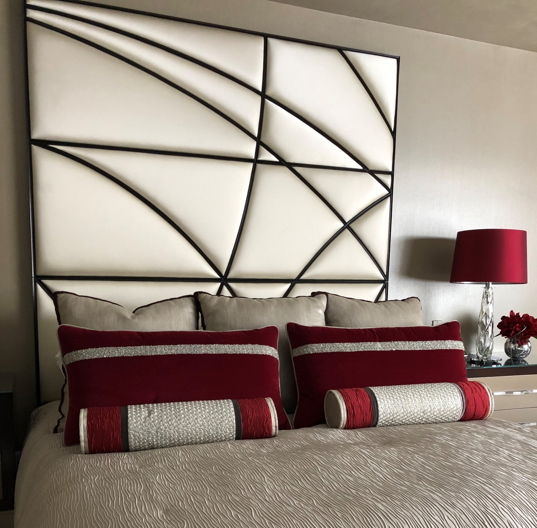 Romantic red pillows heighten the drama of the quilted head board.