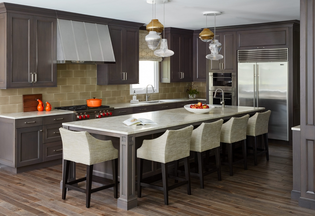 stained wood kitchen with island, counter stools, range hood, pendant lights