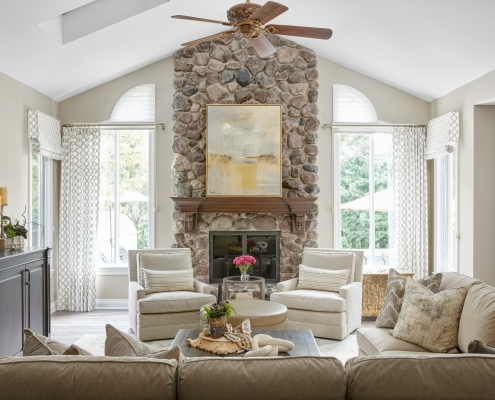 Great room with stone fireplace, window treatment panels, sofas, chairs, TV, cocktail table, accessories