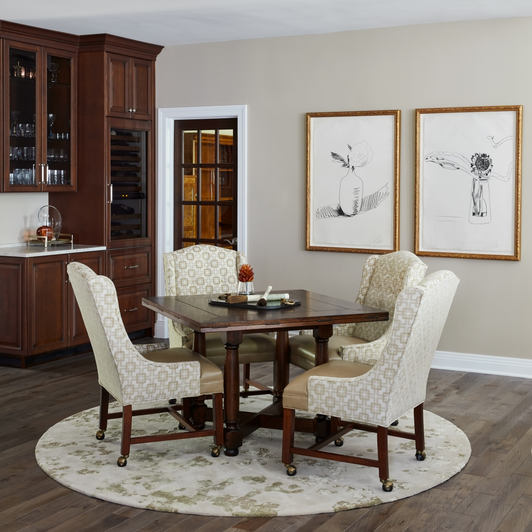 Game table with chairs, rug, wall art, home bar