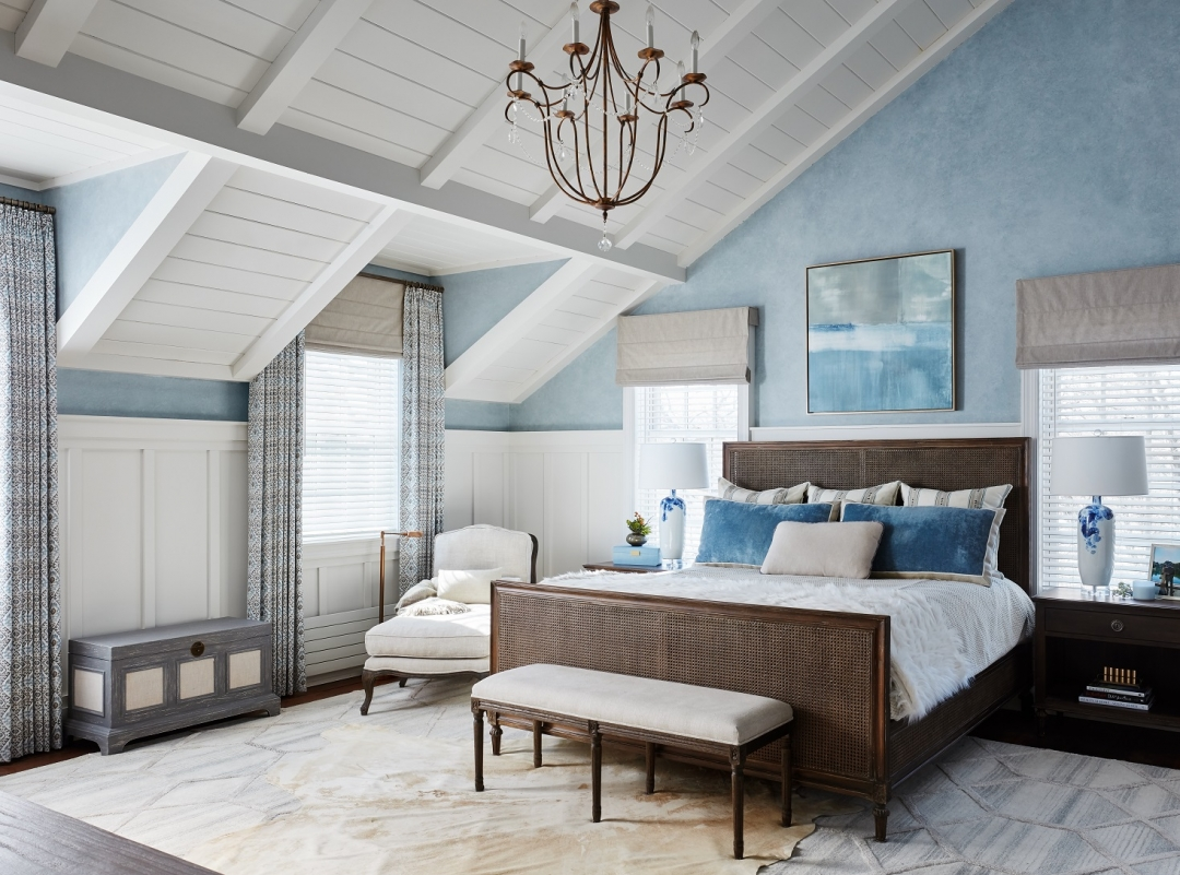 modern coastal bedroom, blue and white bedroom, upholstered bench, pillows, chandelier, bed, rug, wall art