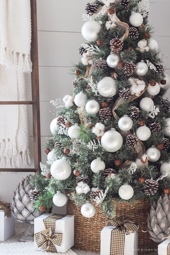 outdoor christmas tree, wicker basket, pine cones on outdoor christmas tree, white ornaments, gifts, flocked branches, bell ornaments