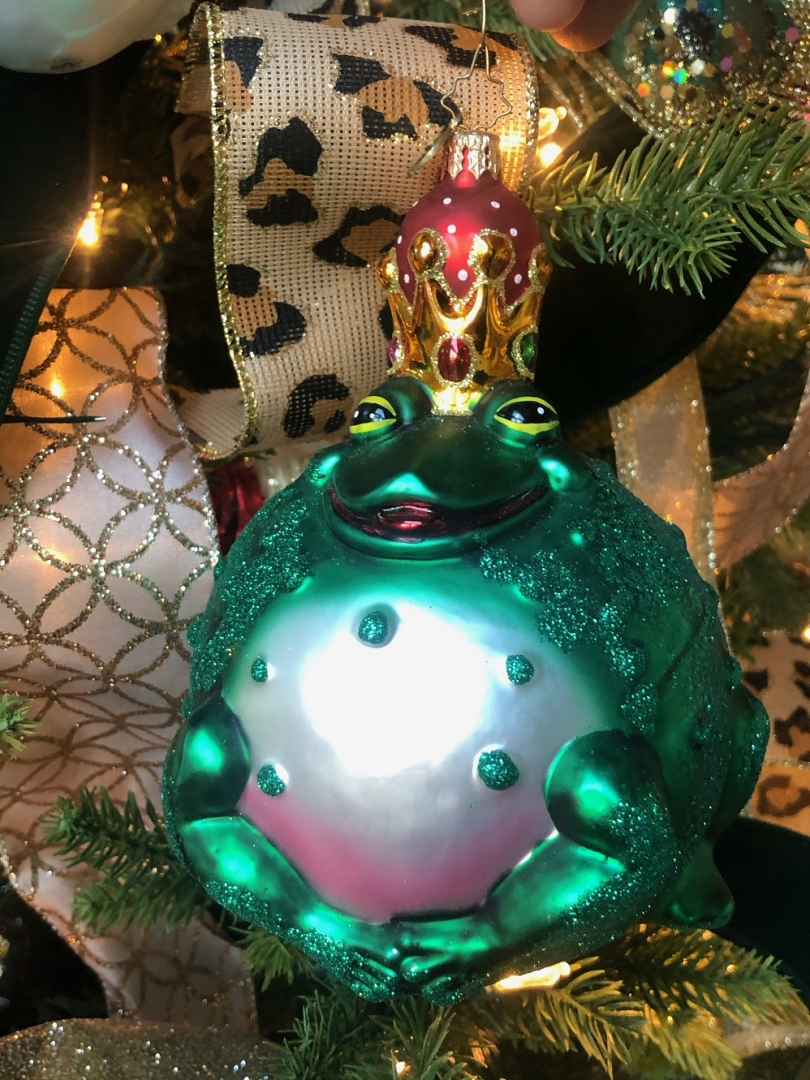 closeup of frog ornament on christmas tree, ribbons