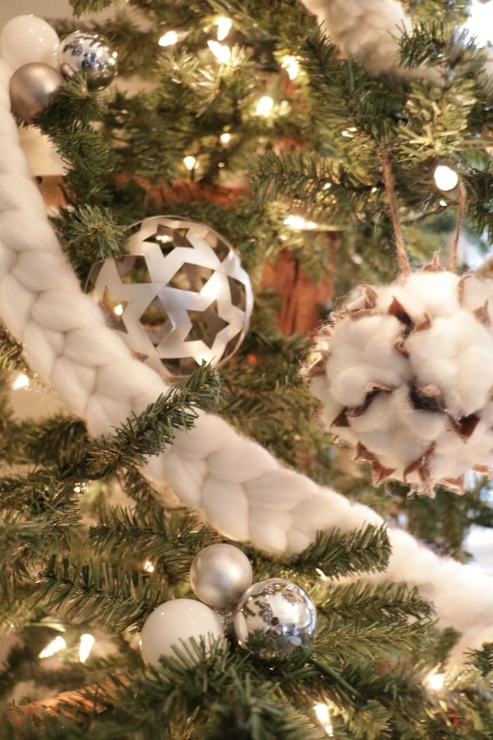 closeup of christmas tree, white cotton braided garland, ornaments