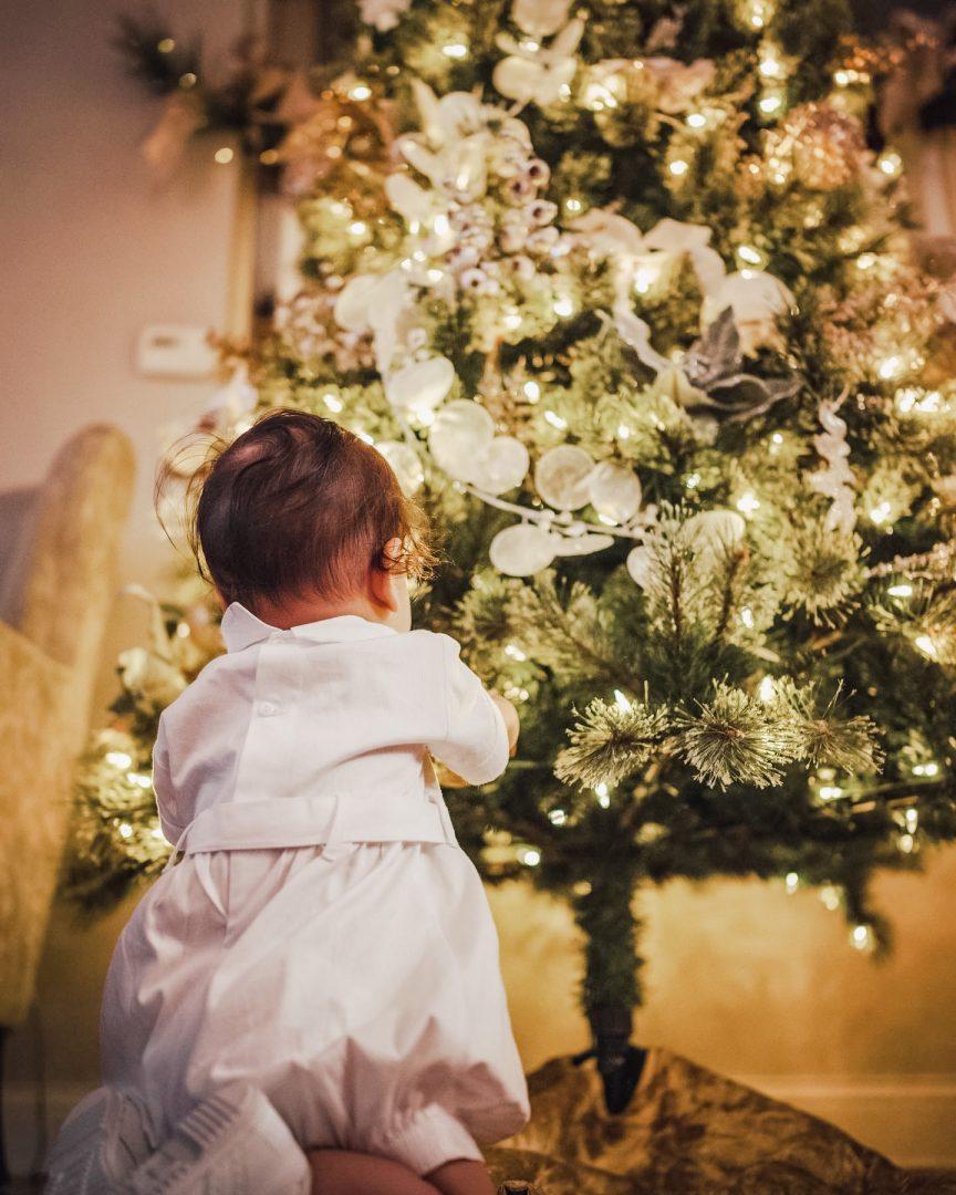 closeup of baby boy touching a christmas tree