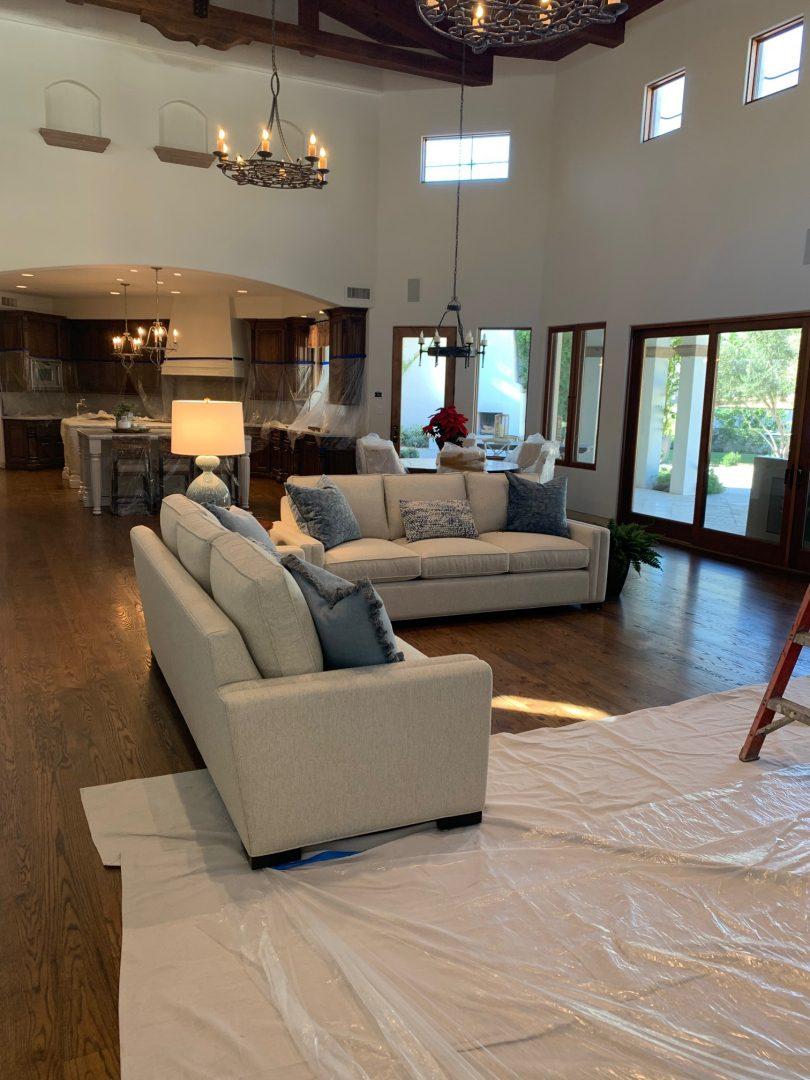 great room, sofas, wood floor, windows, chandeliers