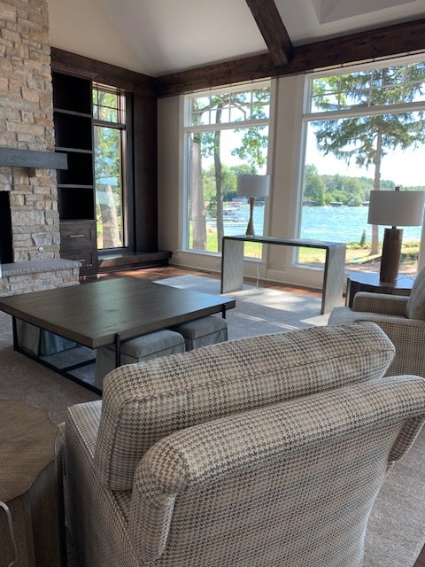 great room, arm chairs, cocktail table, ottos, windows, lake, console table, lamp, fireplace