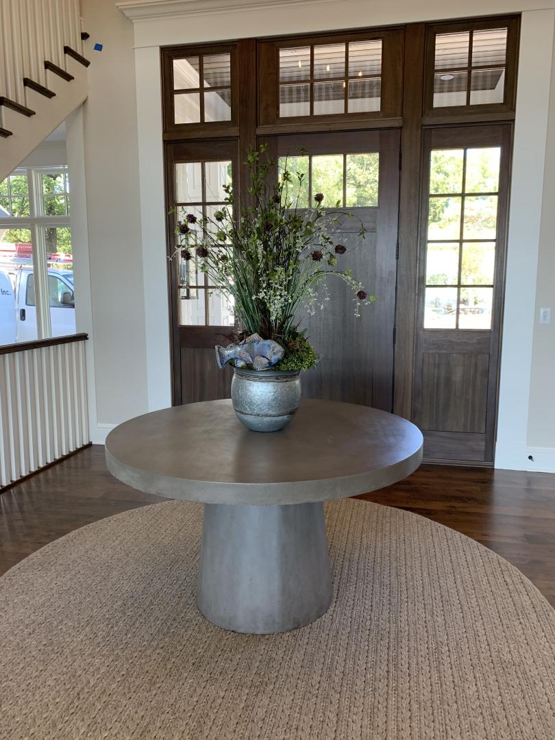foyer, cement table, vase, rug, doorway, wood floor, wild flowers