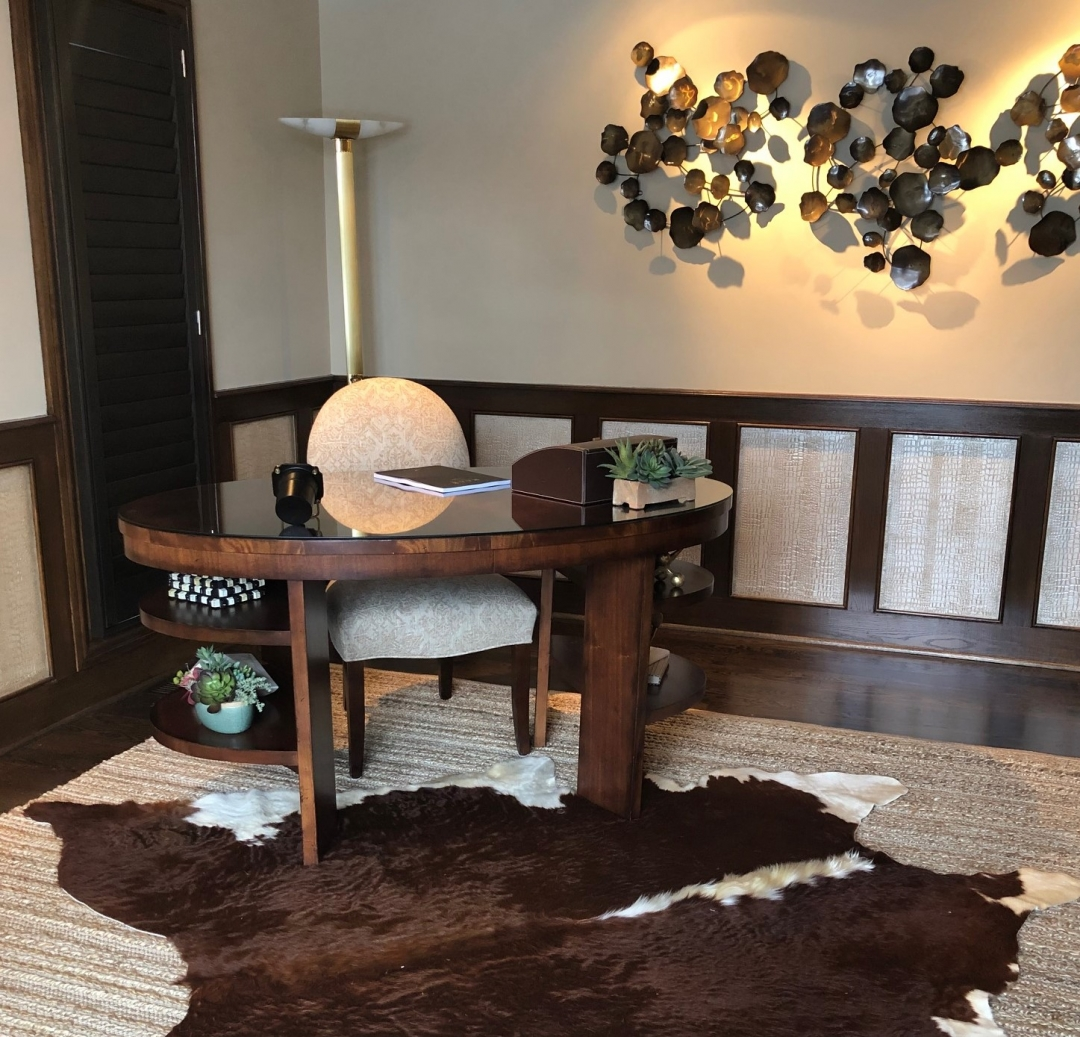 home office, oval desk, desk chair, wainscot insets, cowhide, sisal rug, wall art
