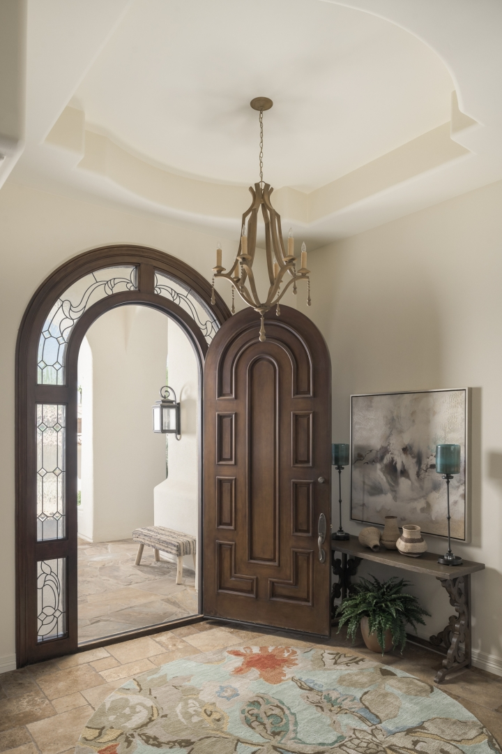 front entry, botanical rug, arched doorway, chandelier, chest, wall art, accessories