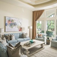 family room, two sofas, cocktail table, arm chair, pillows, wall art, floor lamp, wood sculpture, window panels, rug