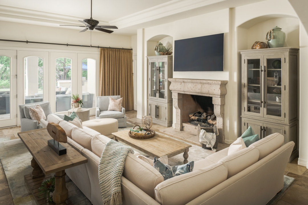 living room, fire place, sectional sofa, arm chairs, wall-mounted TV, cocktail table, sofa table, pillows, throw, accessories, ceiling fan, built-in cabinets