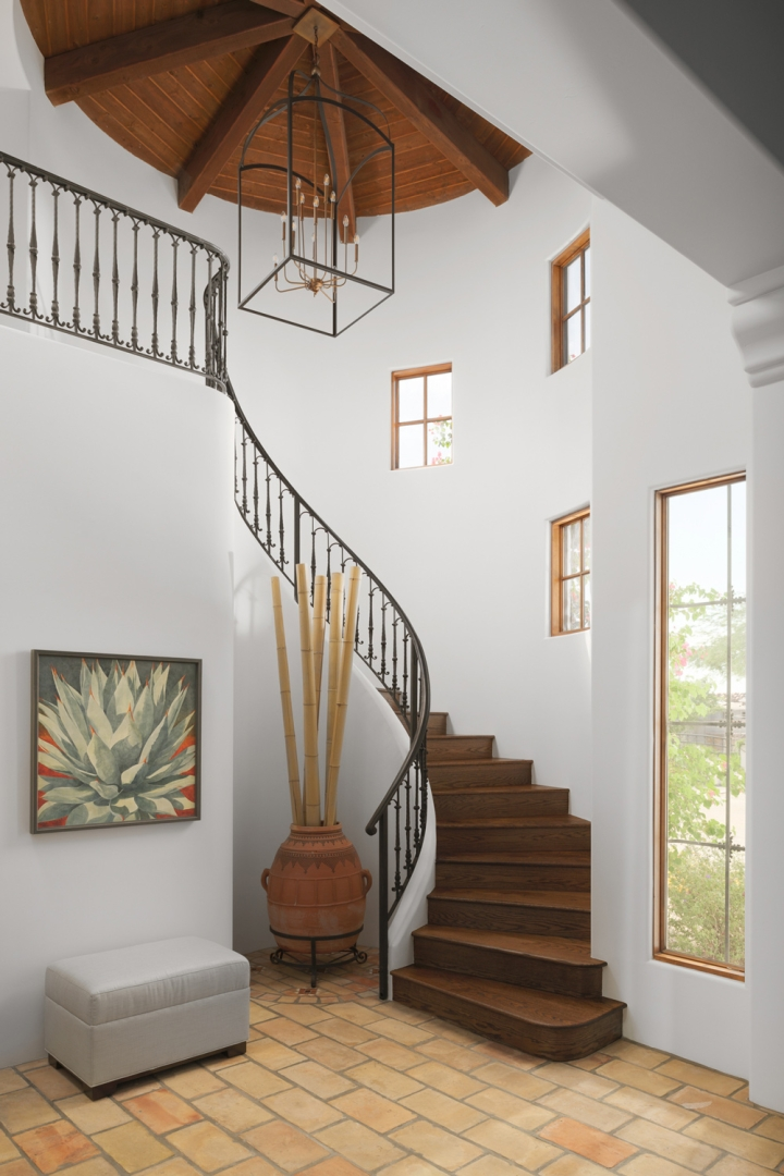 curving stairway, terra cotta tile floor, bench, wall art, clay pot, bamboo branches, large ceiling fixture, wood ceiling, mullioned windows, white walls, wrought iron staircase railing, wood stairs