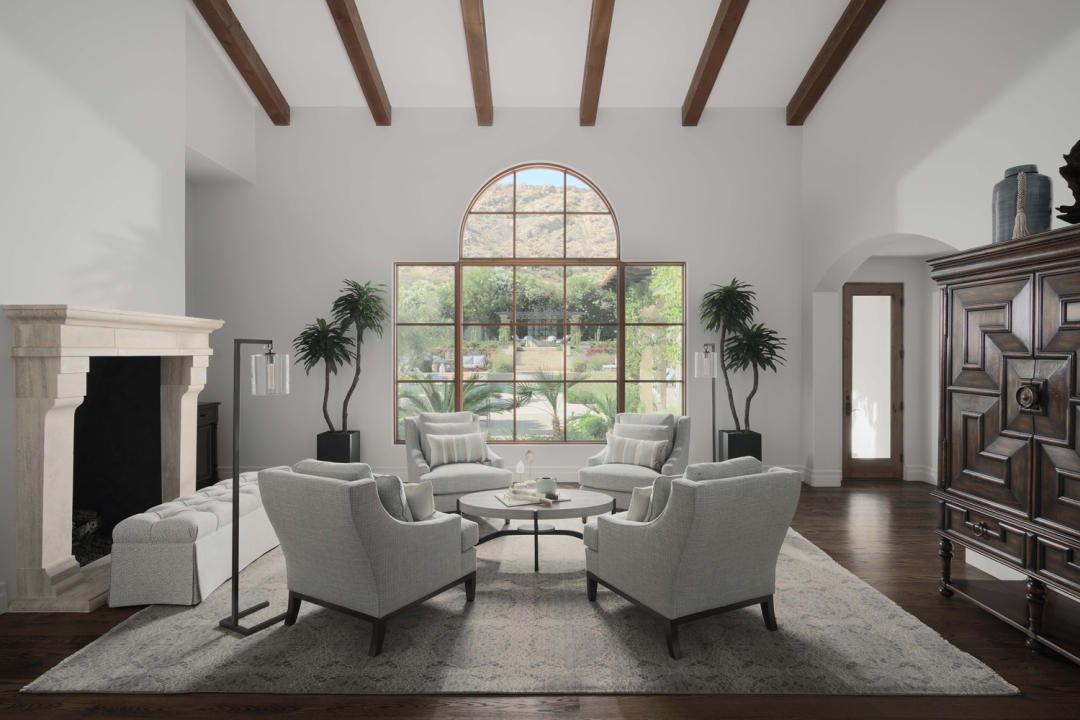 living room, four wing back chairs, long bench, area rug, round cocktail table, wood beam eiling, stone fireplace, potted trees, floor lamp, large chest,