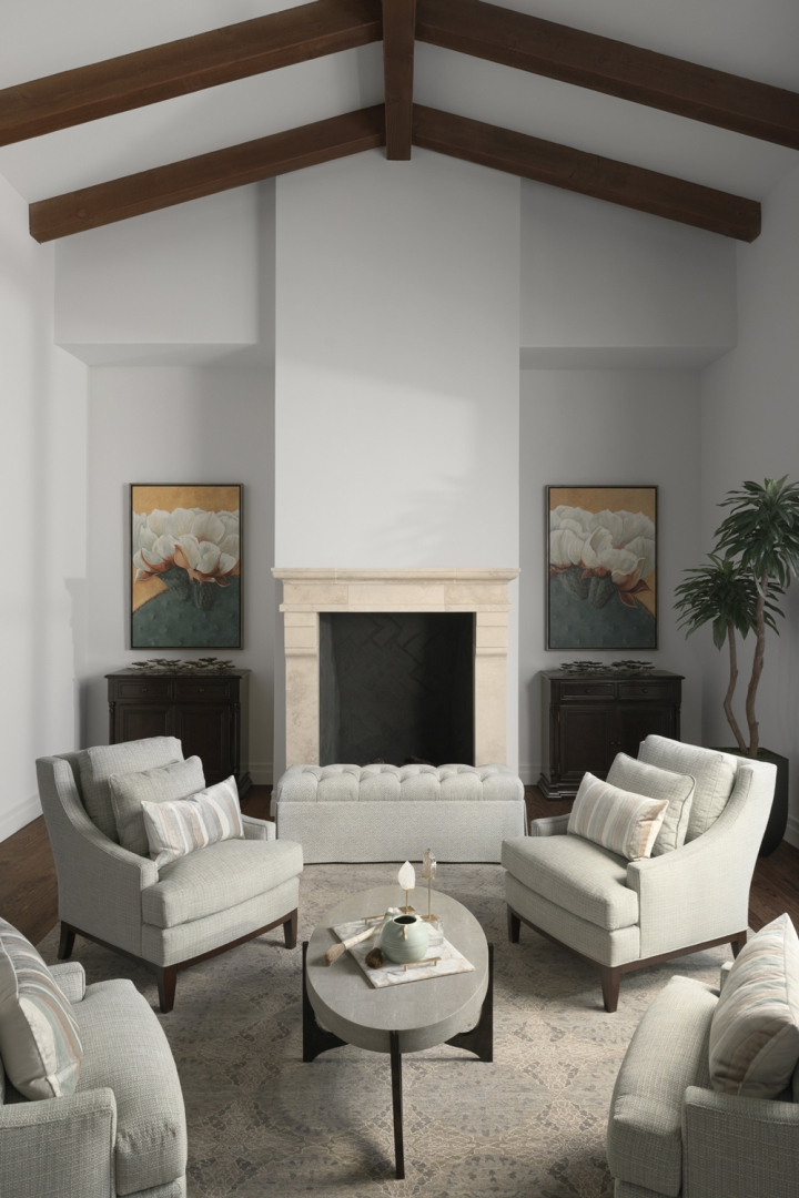 living room, wall art, chests, stone fireplace, tufted bench, wing-back chairs, pillows, oval cocktail table, accessories, rug