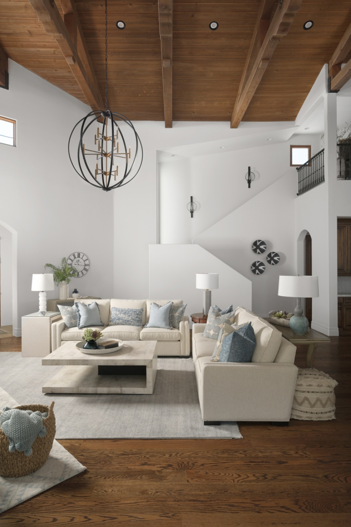 great room, wood ceiling, wood floor, white walls, white sofas, area rug, table lamps, side tables, accesories, wicker basket, sconces